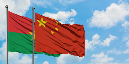 Burkina Faso and China flag waving in the wind against white cloudy blue sky together. Diplomacy concept, international relations.