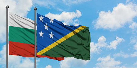 Bulgaria and Solomon Islands flag waving in the wind against white cloudy blue sky together. Diplomacy concept, international relations. Stok Fotoğraf