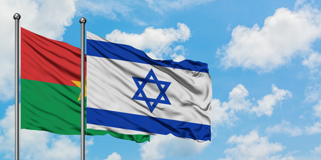 Burkina Faso and Israel flag waving in the wind against white cloudy blue sky together. Diplomacy concept, international relations. Stockfoto