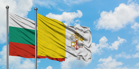 Bulgaria and Vatican City flag waving in the wind against white cloudy blue sky together. Diplomacy concept, international relations. 版權商用圖片