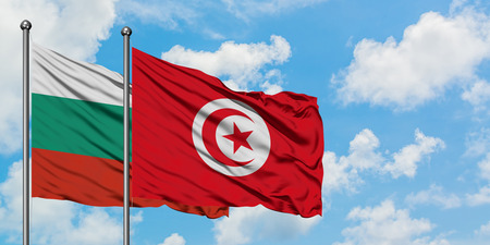 Bulgaria and Tunisia flag waving in the wind against white cloudy blue sky together. Diplomacy concept, international relations.