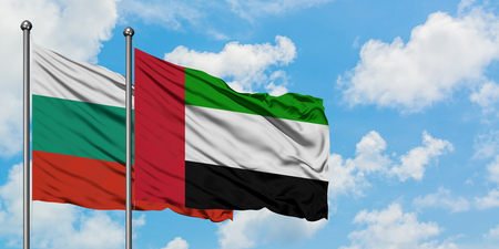 Bulgaria and United Arab Emirates flag waving in the wind against white cloudy blue sky together. Diplomacy concept, international relations.