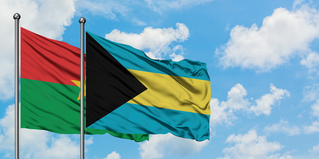 Burkina Faso and Bahamas flag waving in the wind against white cloudy blue sky together. Diplomacy concept, international relations. Stock Photo