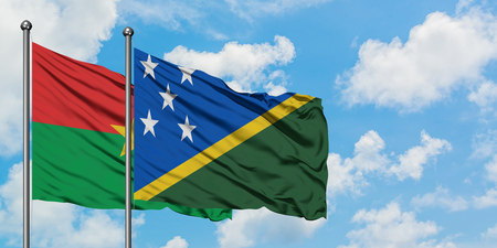 Burkina Faso and Solomon Islands flag waving in the wind against white cloudy blue sky together. Diplomacy concept, international relations.