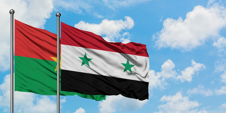 Burkina Faso and Syria flag waving in the wind against white cloudy blue sky together. Diplomacy concept, international relations.
