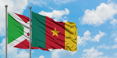 Burundi and Cameroon flag waving in the wind against white cloudy blue sky together. Diplomacy concept, international relations. Stockfoto