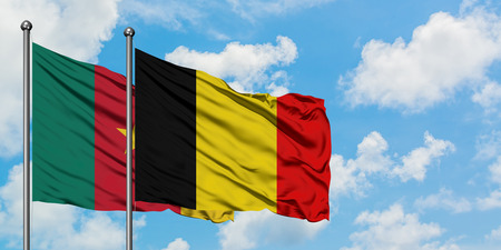 Cameroon and Belgium flag waving in the wind against white cloudy blue sky together. Diplomacy concept, international relations. Stockfoto