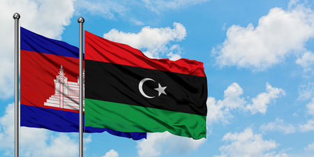 Cambodia and Libya flag waving in the wind against white cloudy blue sky together. Diplomacy concept, international relations.