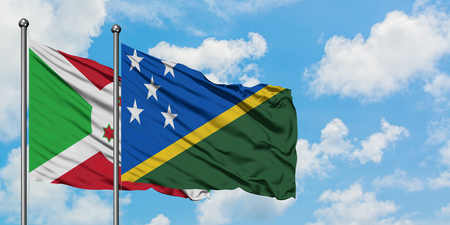 Burundi and Solomon Islands flag waving in the wind against white cloudy blue sky together. Diplomacy concept, international relations.