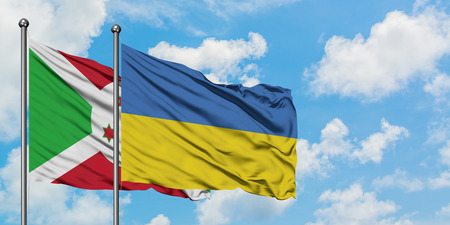 Burundi and Ukraine flag waving in the wind against white cloudy blue sky together. Diplomacy concept, international relations. Stock Photo