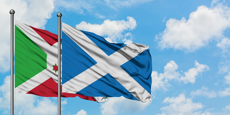 Burundi and Scotland flag waving in the wind against white cloudy blue sky together. Diplomacy concept, international relations.