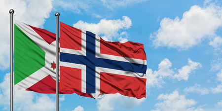 Burundi and Norway flag waving in the wind against white cloudy blue sky together. Diplomacy concept, international relations.