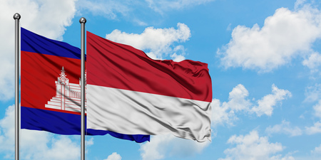 Cambodia and Monaco flag waving in the wind against white cloudy blue sky together. Diplomacy concept, international relations. Stok Fotoğraf