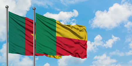 Cameroon and Benin flag waving in the wind against white cloudy blue sky together. Diplomacy concept, international relations.