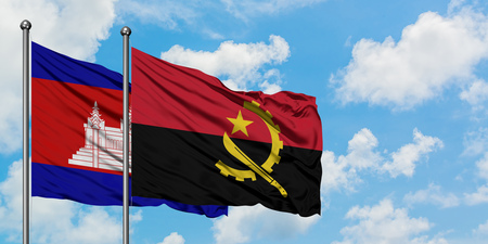 Cambodia and Angola flag waving in the wind against white cloudy blue sky together. Diplomacy concept, international relations.