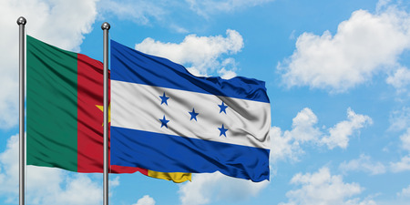 Cameroon and Honduras flag waving in the wind against white cloudy blue sky together. Diplomacy concept, international relations.