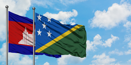 Cambodia and Solomon Islands flag waving in the wind against white cloudy blue sky together. Diplomacy concept, international relations.