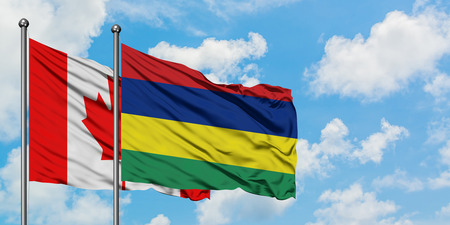 Canada and Mauritius flag waving in the wind against white cloudy blue sky together. Diplomacy concept, international relations. Stock Photo
