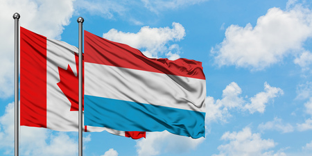 Canada and Luxembourg flag waving in the wind against white cloudy blue sky together. Diplomacy concept, international relations. Stock Photo