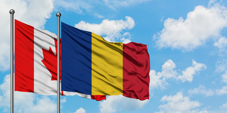 Canada and Romania flag waving in the wind against white cloudy blue sky together. Diplomacy concept, international relations.