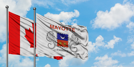 Canada and Mayotte flag waving in the wind against white cloudy blue sky together. Diplomacy concept, international relations.