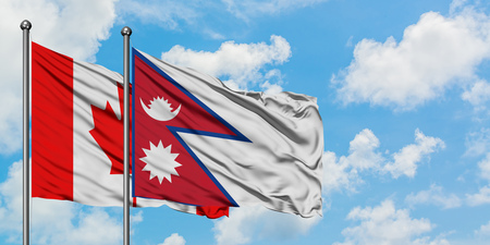 Canada and Nepal flag waving in the wind against white cloudy blue sky together. Diplomacy concept, international relations. Stock Photo