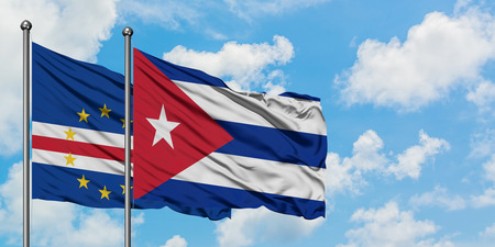 Cape Verde and Cuba flag waving in the wind against white cloudy blue sky together. Diplomacy concept, international relations. Stock Photo