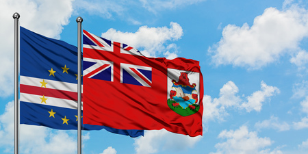 Cape Verde and Bermuda flag waving in the wind against white cloudy blue sky together. Diplomacy concept, international relations. Imagens