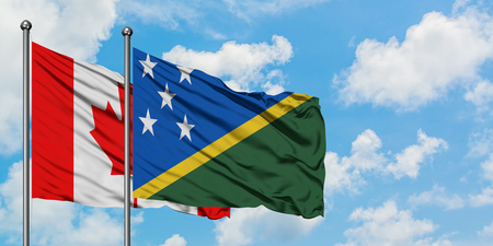 Canada and Solomon Islands flag waving in the wind against white cloudy blue sky together. Diplomacy concept, international relations. Stock Photo