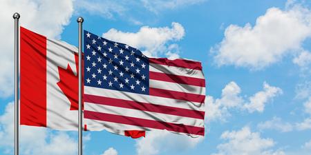 Kanada und die Vereinigten Staaten Fahnenschwingen im Wind gegen weißen bewölkten blauen Himmel zusammen. Diplomatie-Konzept, internationale Beziehungen.