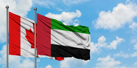 Canada and United Arab Emirates flag waving in the wind against white cloudy blue sky together. Diplomacy concept, international relations. Stock Photo
