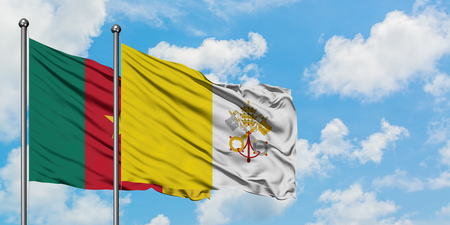 Cameroon and Vatican City flag waving in the wind against white cloudy blue sky together. Diplomacy concept, international relations.
