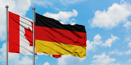 Canada and Germany flag waving in the wind against white cloudy blue sky together. Diplomacy concept, international relations.