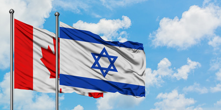Canada and Israel flag waving in the wind against white cloudy blue sky together. Diplomacy concept, international relations.
