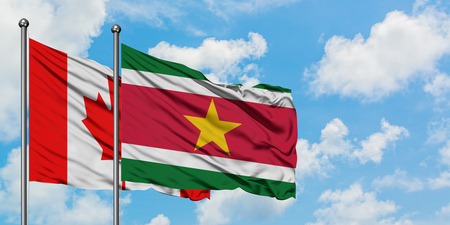 Canada and Suriname flag waving in the wind against white cloudy blue sky together. Diplomacy concept, international relations.