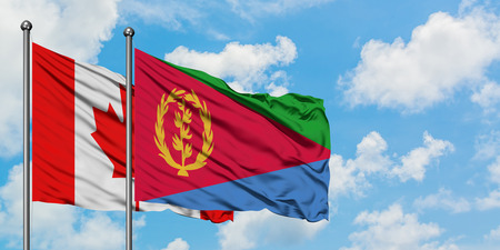 Canada and Eritrea flag waving in the wind against white cloudy blue sky together. Diplomacy concept, international relations. 스톡 콘텐츠