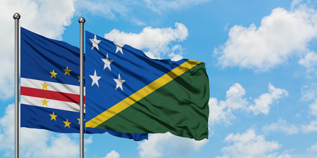 Cape Verde and Solomon Islands flag waving in the wind against white cloudy blue sky together. Diplomacy concept, international relations.