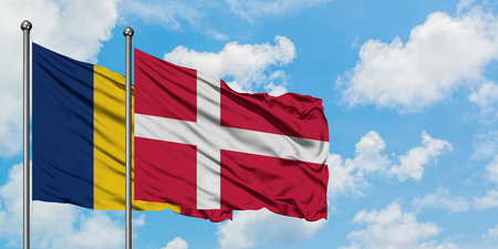 Chad and Denmark flag waving in the wind against white cloudy blue sky together. Diplomacy concept, international relations. Archivio Fotografico