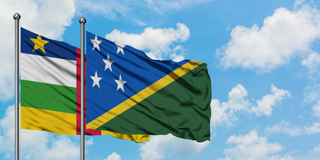 Central African Republic and Solomon Islands flag waving in the wind against white cloudy blue sky together. Diplomacy concept, international relations.