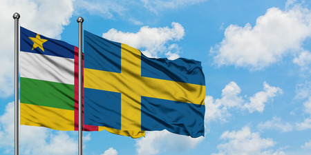 Central African Republic and Sweden flag waving in the wind against white cloudy blue sky together. Diplomacy concept, international relations. Stock Photo