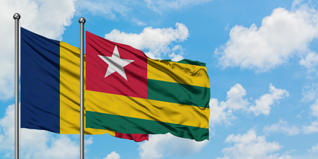 Chad and Togo flag waving in the wind against white cloudy blue sky together. Diplomacy concept, international relations.