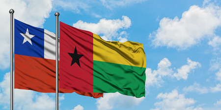 Chile and Guinea Bissau flag waving in the wind against white cloudy blue sky together. Diplomacy concept, international relations. Stock fotó