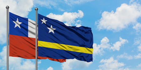 Chile and Curacao flag waving in the wind against white cloudy blue sky together. Diplomacy concept, international relations.