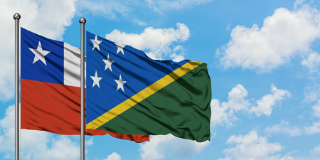 Chile and Solomon Islands flag waving in the wind against white cloudy blue sky together. Diplomacy concept, international relations.