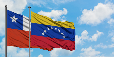 Chile and Venezuela flag waving in the wind against white cloudy blue sky together. Diplomacy concept, international relations. Фото со стока