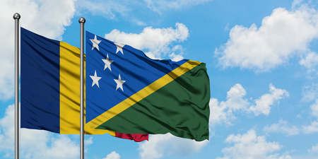 Chad and Solomon Islands flag waving in the wind against white cloudy blue sky together. Diplomacy concept, international relations.