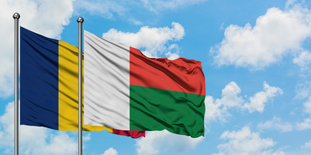 Chad and Madagascar flag waving in the wind against white cloudy blue sky together. Diplomacy concept, international relations. Archivio Fotografico