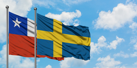 Chile and Sweden flag waving in the wind against white cloudy blue sky together. Diplomacy concept, international relations.