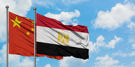 China and Egypt flag waving in the wind against white cloudy blue sky together. Diplomacy concept, international relations. Stock Photo