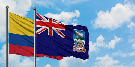 Colombia and Falkland Islands flag waving in the wind against white cloudy blue sky together. Diplomacy concept, international relations.